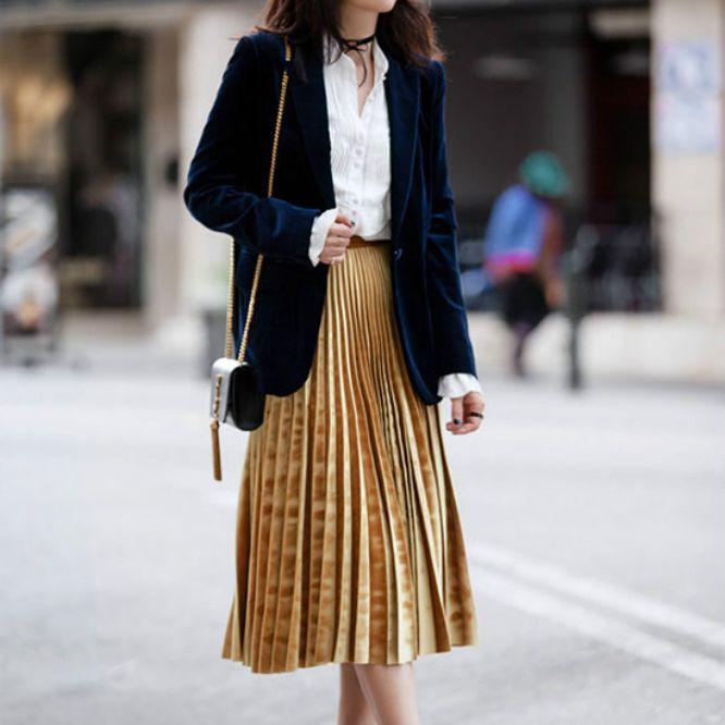 Street style woman in pleated skirt and velvet blazer