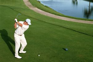 Golfer teeing off next to blue tee marker.