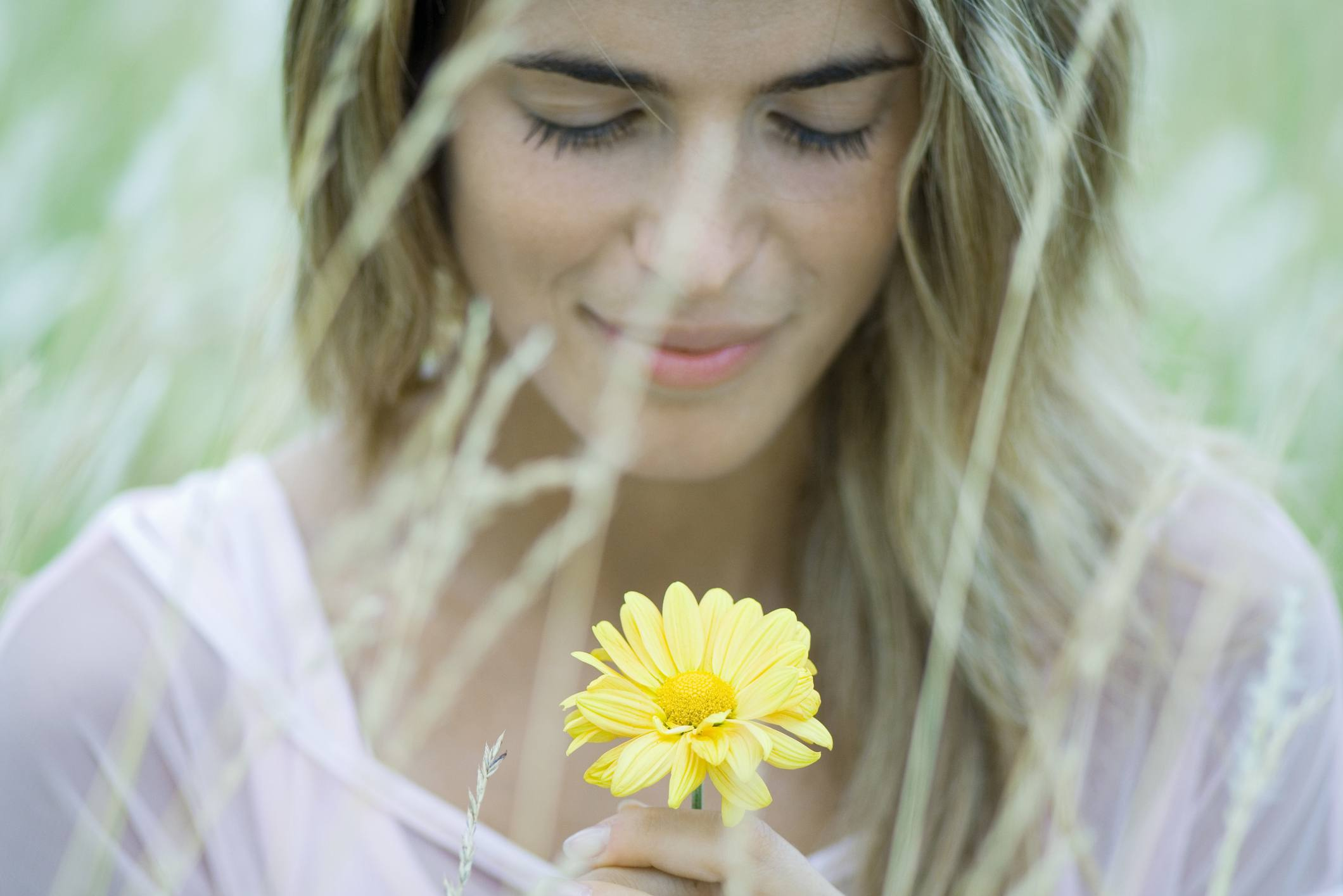 Woman with blond hair looking at flower