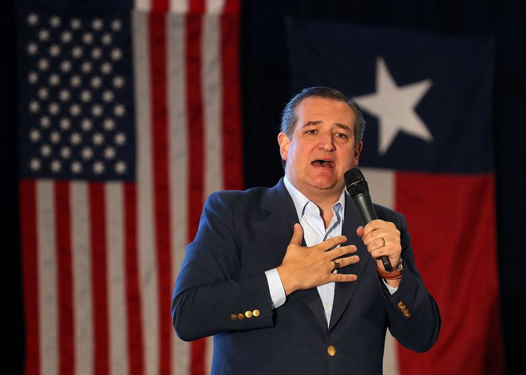 Ted Cruz holding a microphone and standing before the U.S. and Texas state flags.