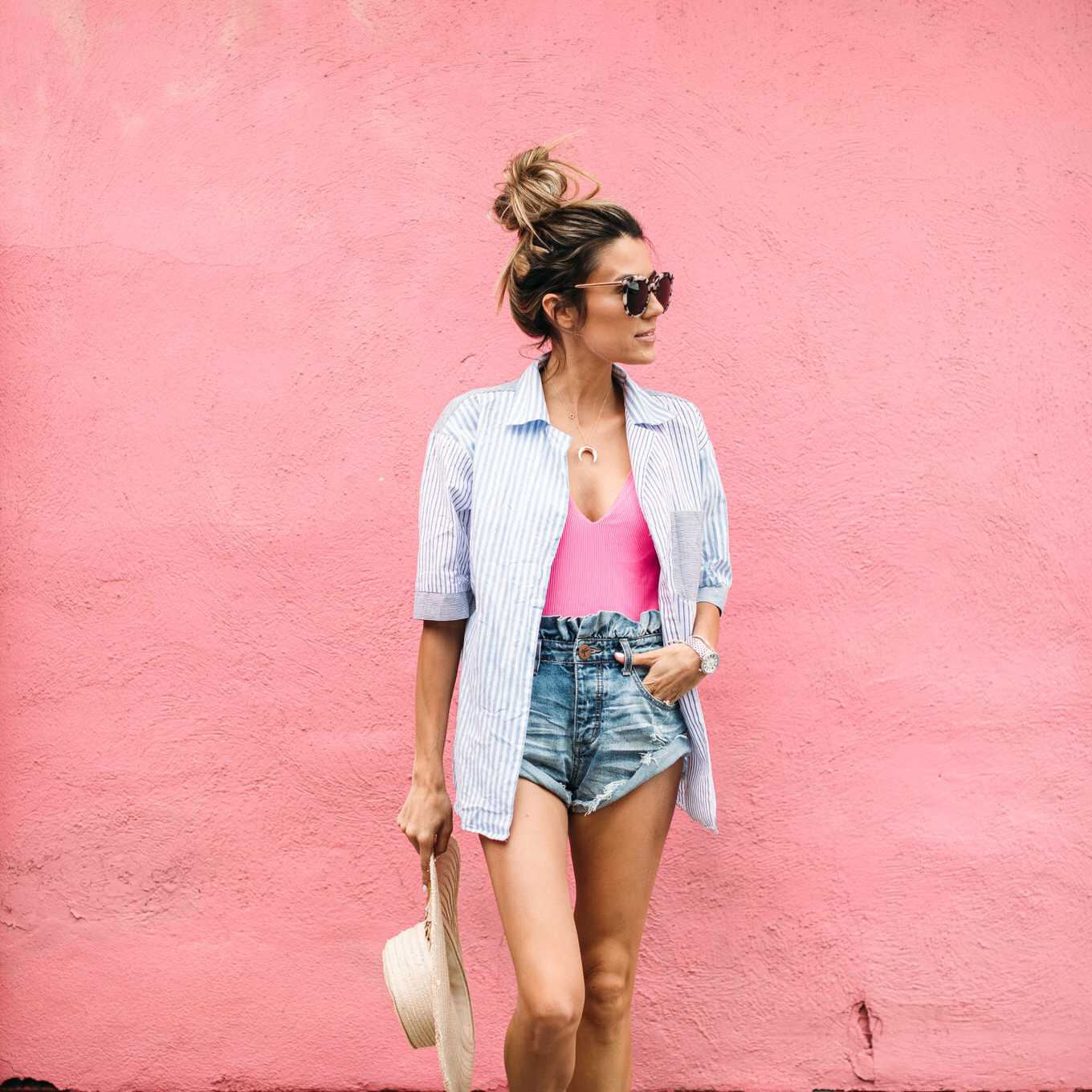Woman in denim shorts and button-down shirt for summer fashion