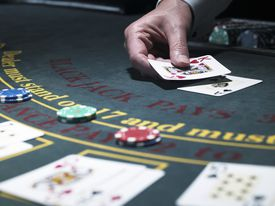 Male croupier holding card at Blackjack table, close-up