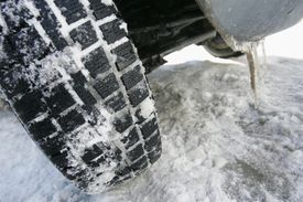 Car tire with snow and icicles