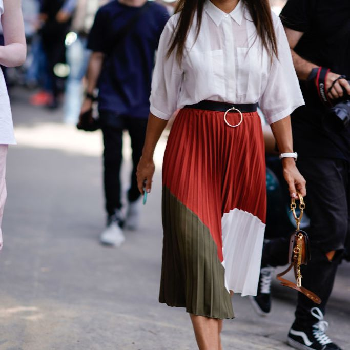 Woman wearing white shirt and pleated skirt street style