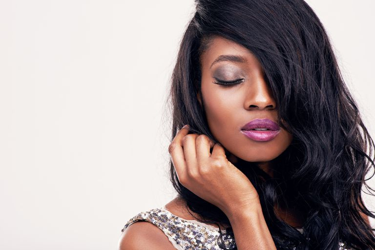 Black woman with pink lipstick and silver eyeshadow on, wearing a silver sequin dress, in front of a white background