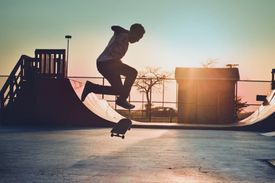 Skateboarder, in midair, preparing to land a trick