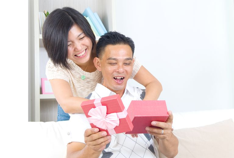 Happy Couple Looking At Gifts In Home