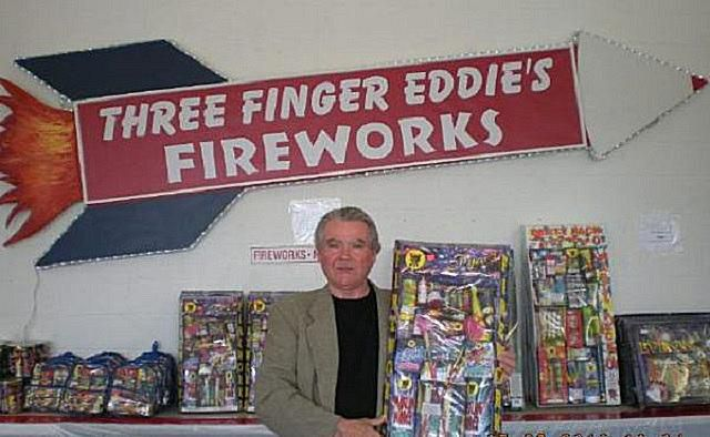 A man displays fireworks near a sign for