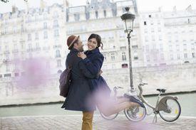 A couple embraces along the Seine River in Paris