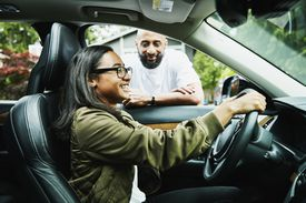 A teenaged driver sits behind the wheel as her father looks on.