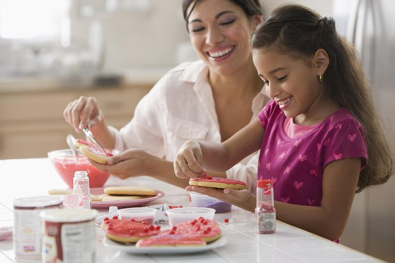 Woman and daughter decorating Valentine's Day cookies.