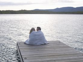 A Couple Snuggled by a Lake