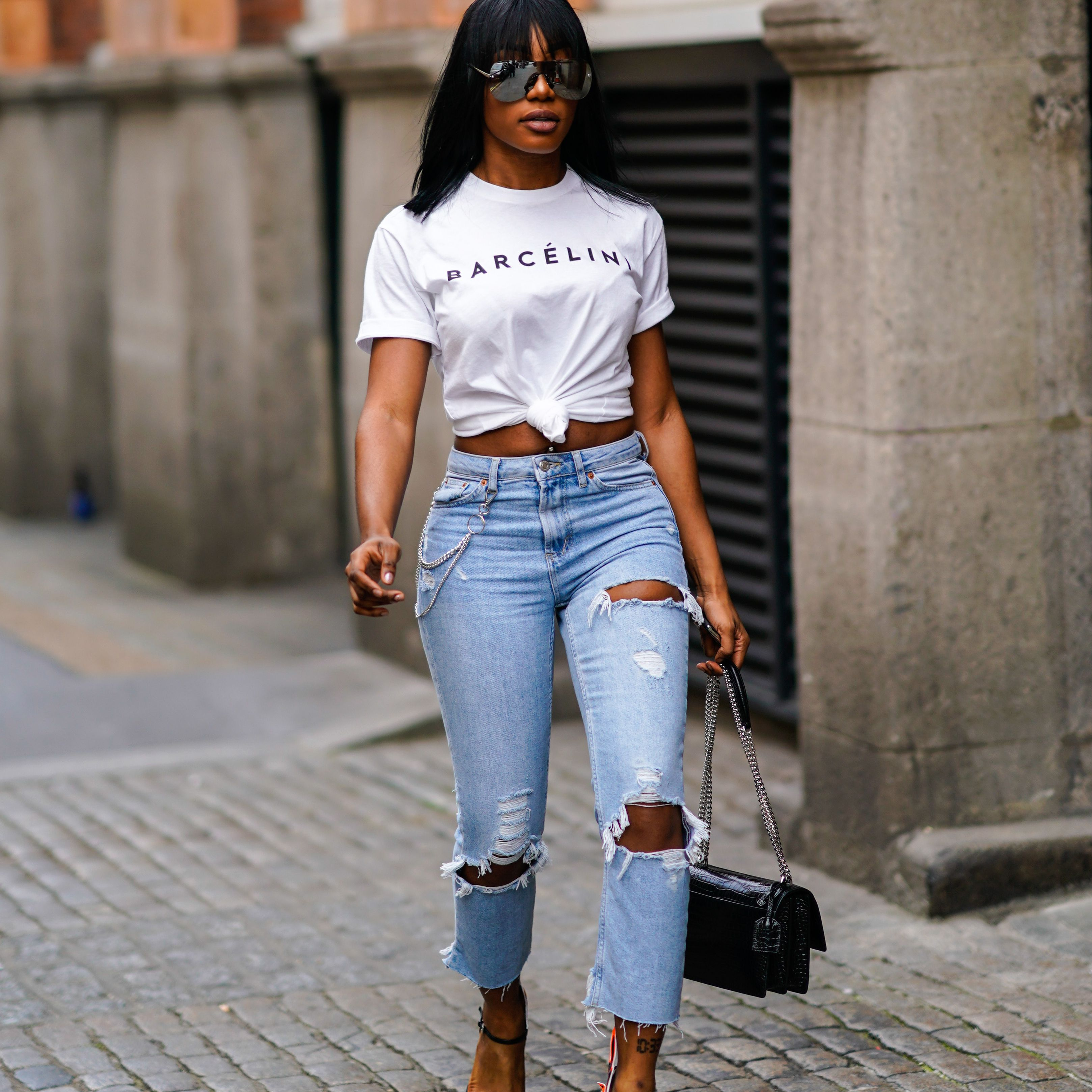 32146bdfb Street style woman in ripped jeans and t-shirt and black leather purse