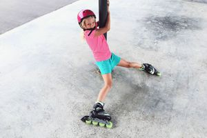 Girl clings to pole while trying to roller blade