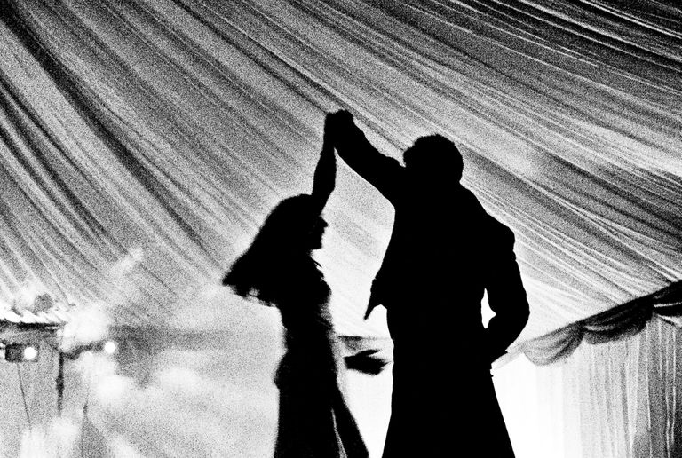 Bride and groom silhouetted against the background during their first dance.
