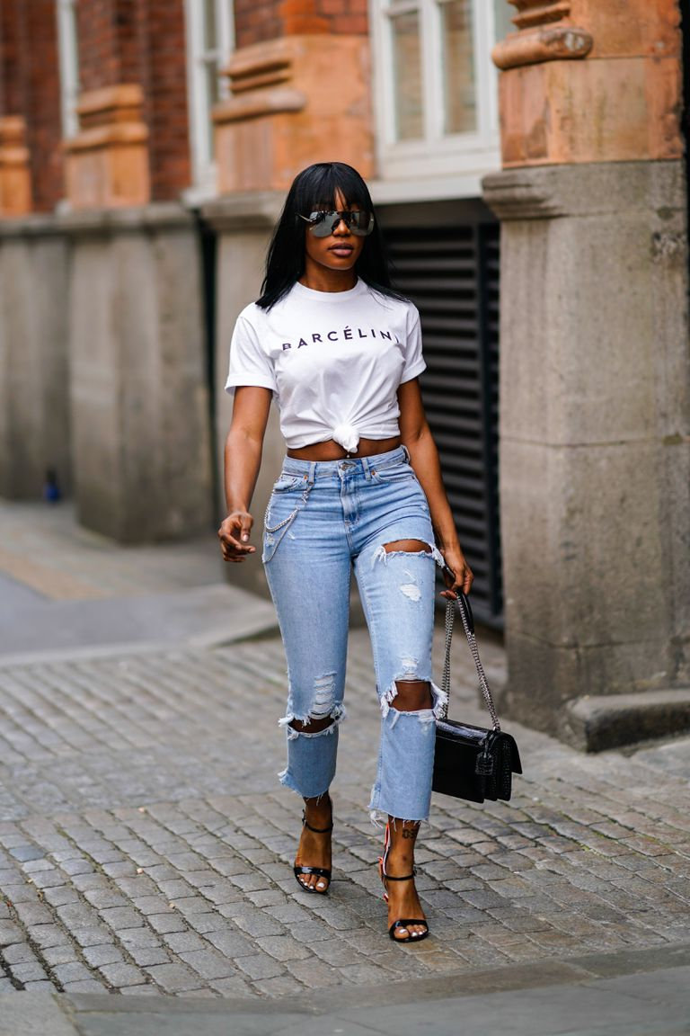 3eee313d7ff3 Street style woman in ripped jeans and t-shirt and black leather purse