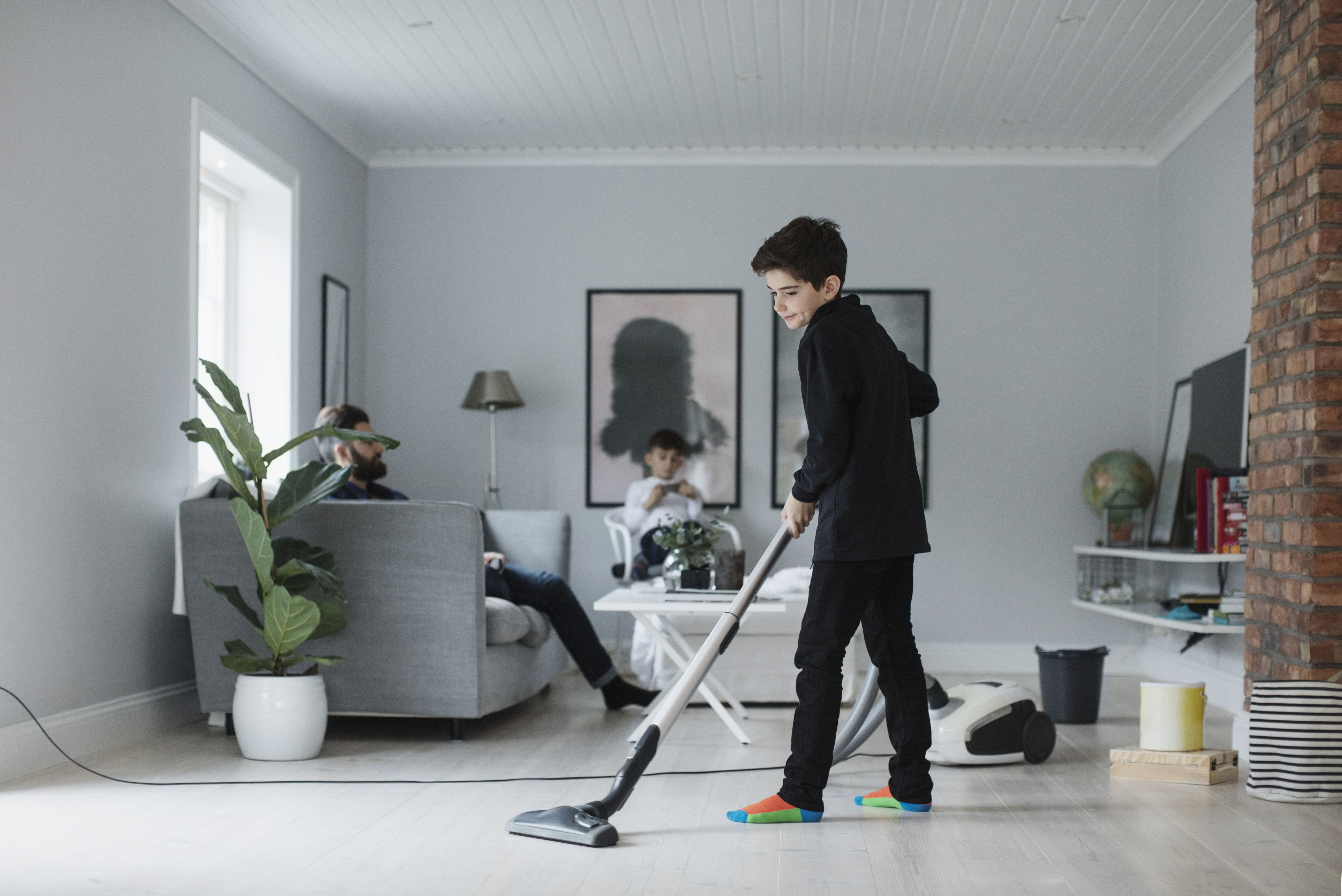 Boy vacuuming floor in living room at home and earning money for the chore.