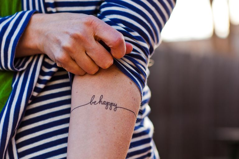 Woman's arm with 'be happy' on it as first tattoo