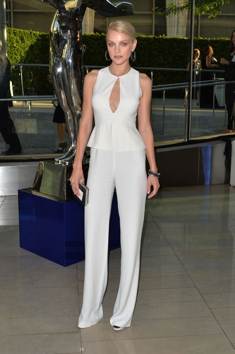 Jessica Stam, in white jumpsuit and dark sandals, attending the 2014 CFDA fashion awards.