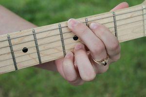Hand at guitar fretboard