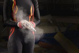 Female gymnast chalking hands