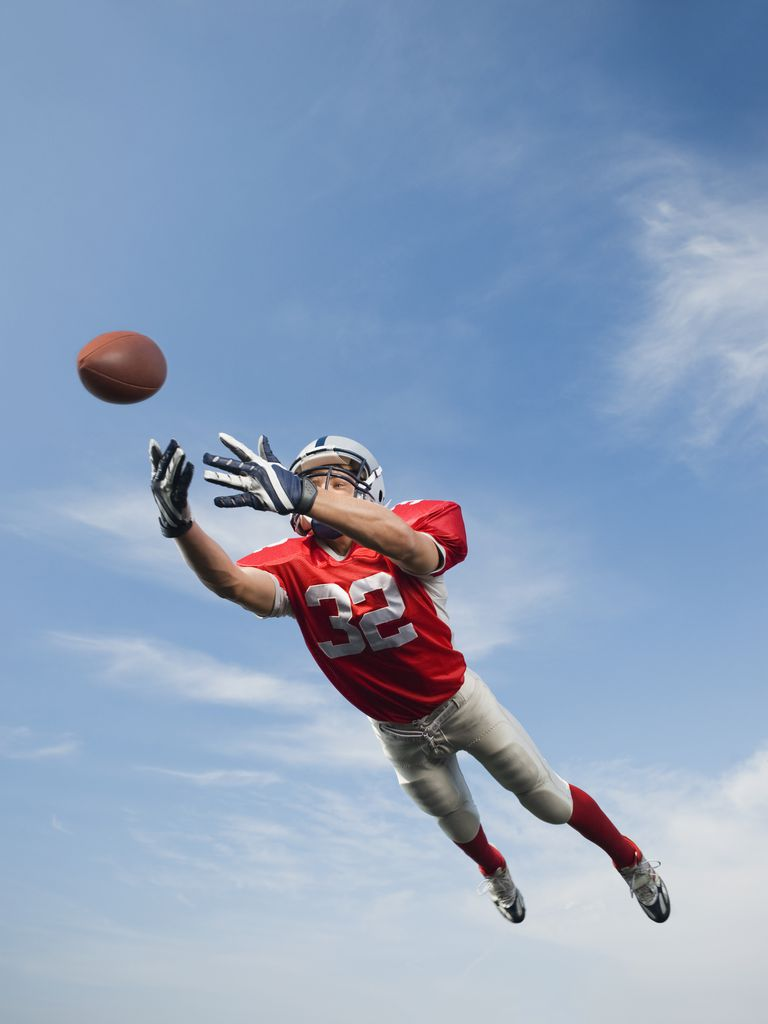 Football player in mid-air reaching for football
