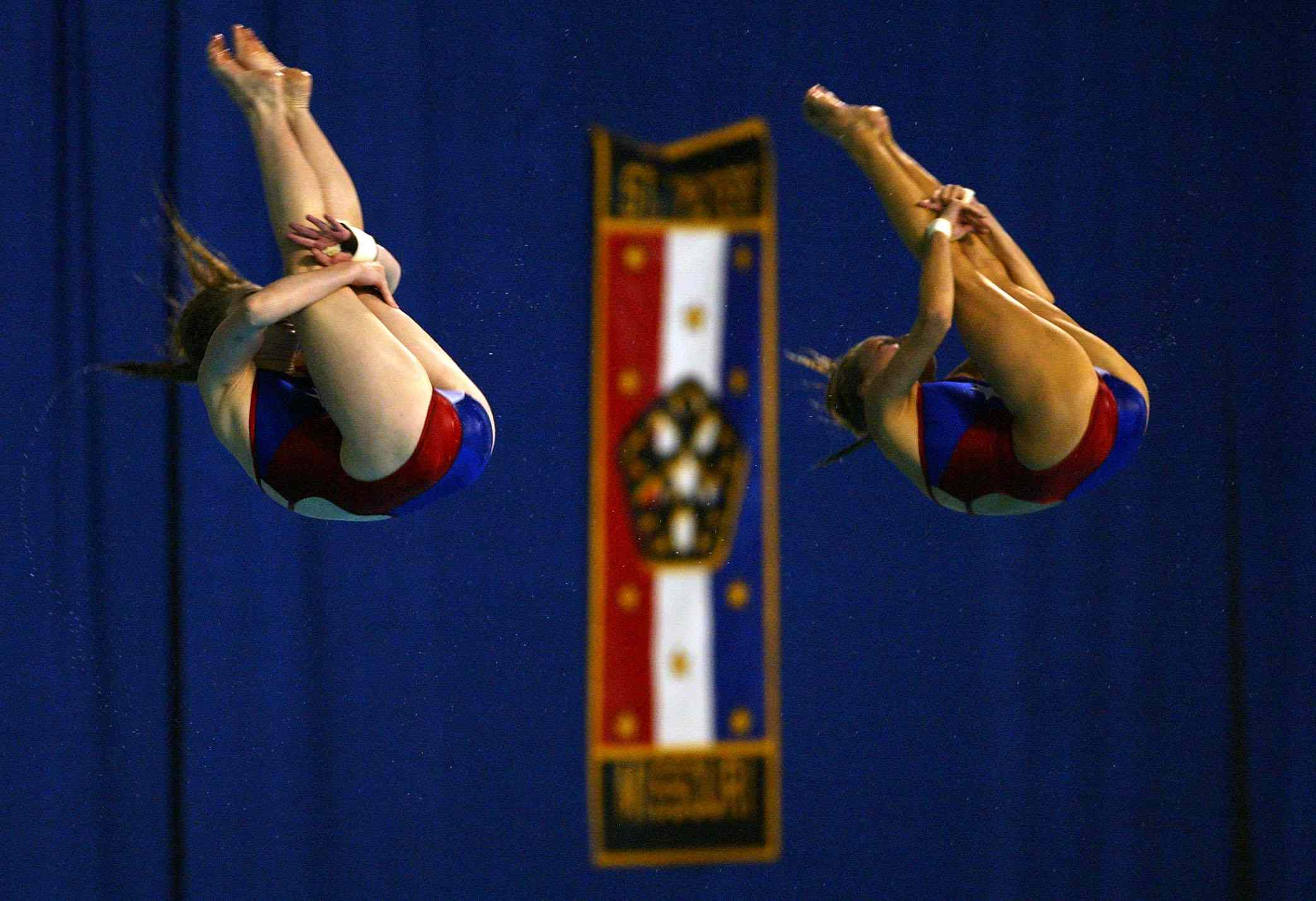 Synchronized divers performing somersaults.