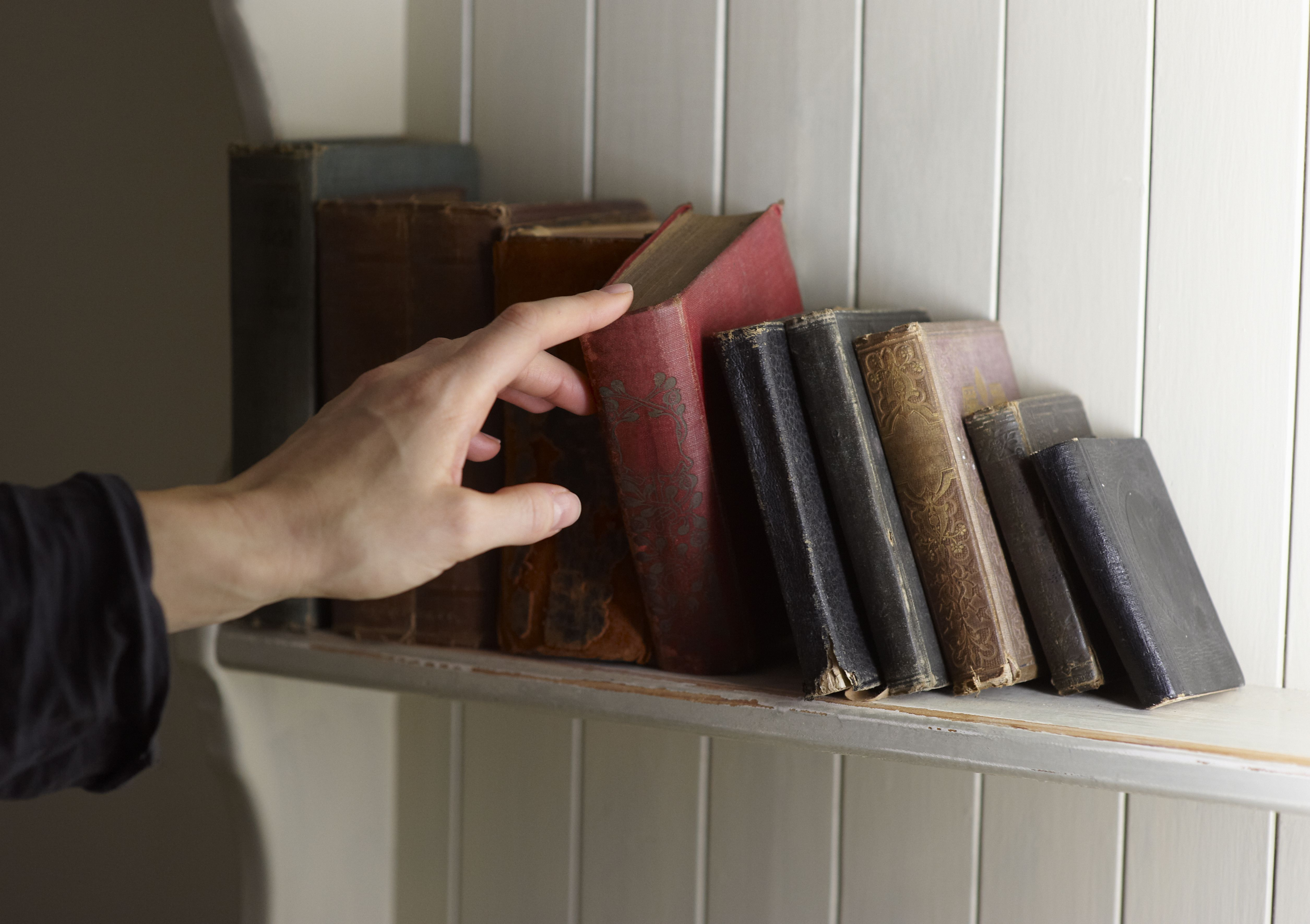 Hand selecting book from shelf