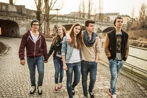 Five teenagers walking together beside river