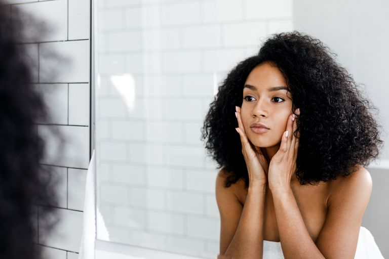 https://www.gettyimages.com/detail/photo/mixed-race-woman-massaging-her-face-and-looking-at-royalty-free-image/875307848