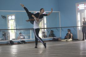 Two people dancing ballet with onlookers