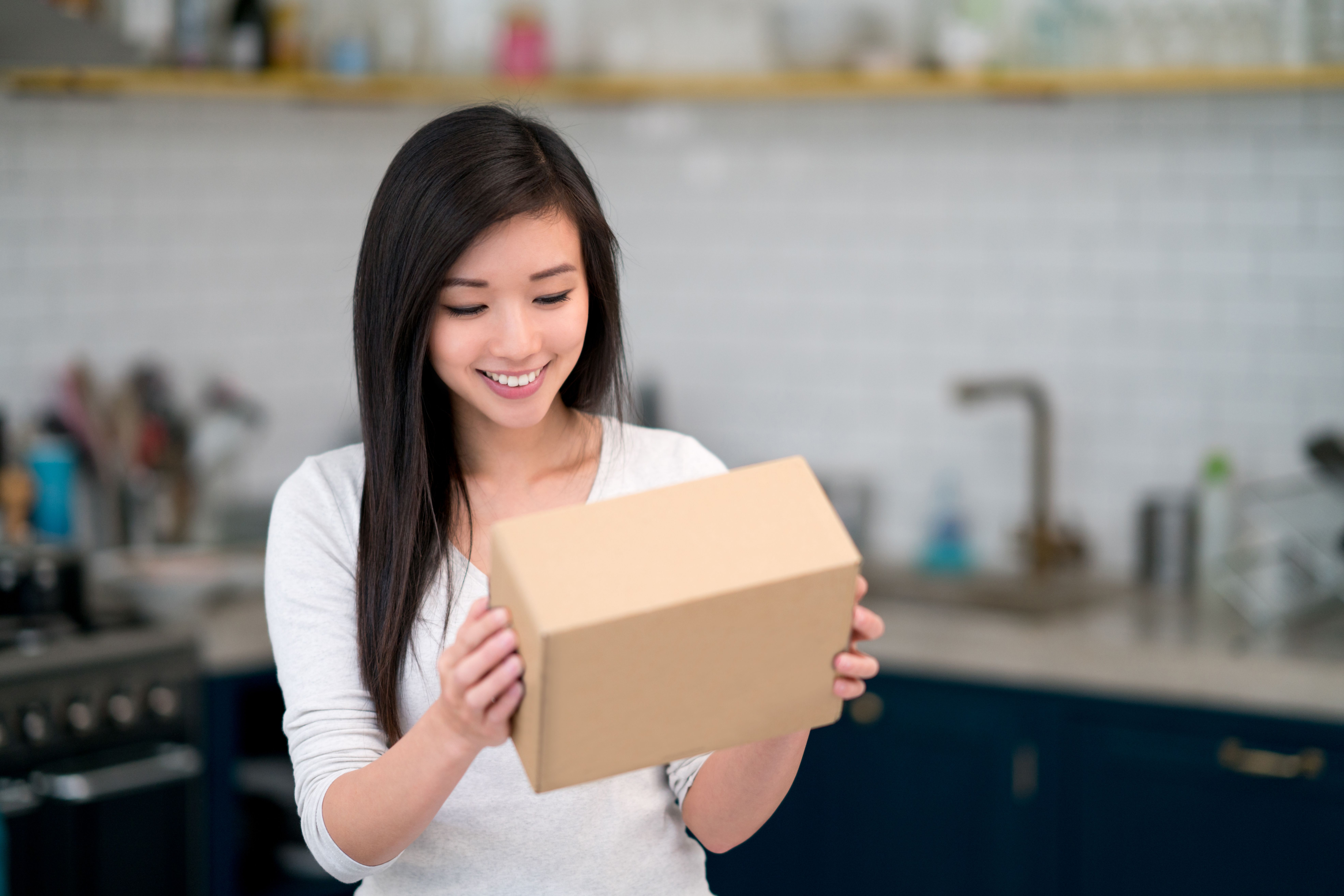 Woman looking at a parcel in her kitchen
