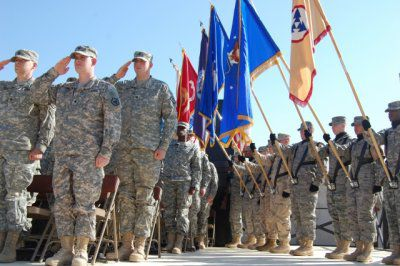 Soldiers and members of a joint color guard render honors prior to a ceremony commemorating Veterans Day
