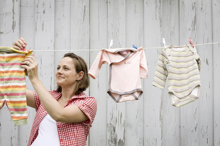 Pregnant woman hanging rompers on clothesline, Munich, Bavaria, Germany