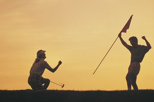 Two golfers celebrating in silhouette