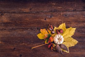 High Angle View Of Autumn Leaves With Food On Wooden Table
