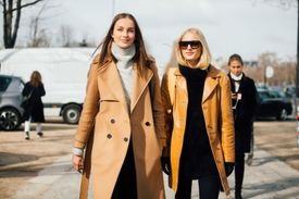 Two women wearing camel coats