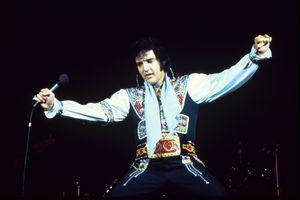 Elvis Presley dancing during performance holding microphone