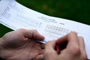 a pair of hands writing down golf scores