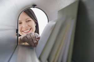 Woman reaching into mailbox for mail