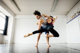 Young modern dancing couple performing in a run down dancing studio