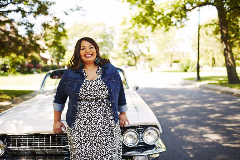 smiling woman leaning against car