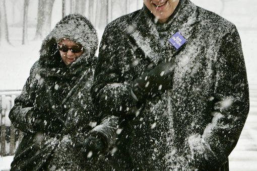 Snow falls on pedestrians