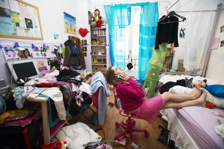 Young Woman Sits on a Chair in a Messy Bedroom Using a Mobile Phone