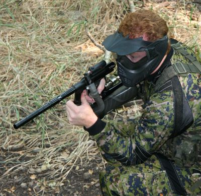 Man with paintball gun and mask.