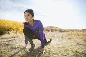 Runner stretching in sunny rural field