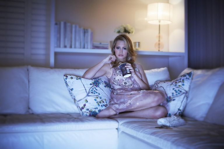 Woman eating ice cream on sofa