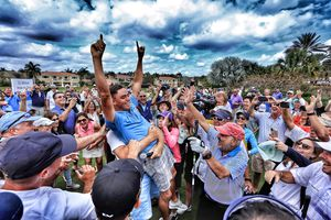 Rickie Fowler celebrates with spectators after his ace won a million dollars for the Els for Autism Foundation
