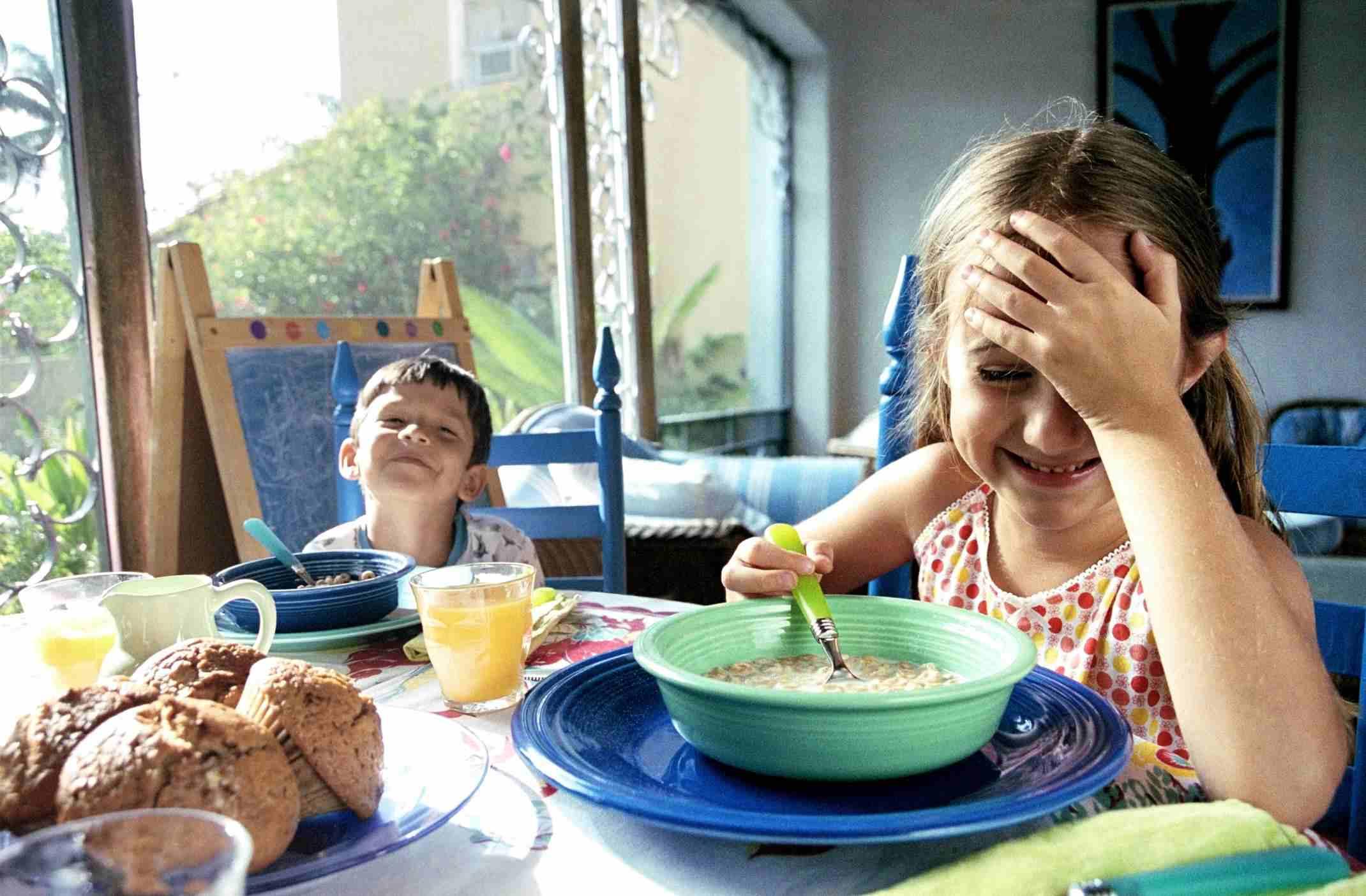 Children smiling at breakfast table