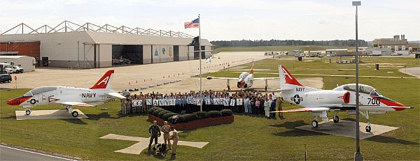 Sailors, Marines, and civilian Department of Defense employees stand in formation while filming a television spot in front of the jet hanger for Training Air Wing One (TW-1) at Naval Air Station Meridian for broadcast during the Army-Navy football game.